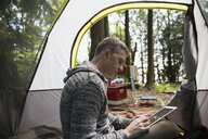 Man using digital tablet inside camping tent - HEROF18807