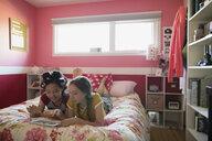 Girls using digital tablet on bed - HEROF18879