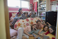 Girls using laptop and digital tablet at slumber party in bedroom - HEROF18897