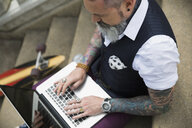 Hipster with tattoos typing on laptop on stair - HEROF18900