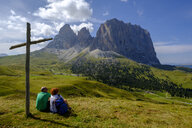 Italy, South Tyrol, Sella group, hiker sitting at summit cross - LBF02356