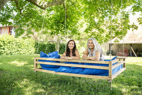 Portrait of two smiling women relaxing on a hanging bed in garden - PESF01261
