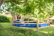 Two women relaxing on a hanging bed in garden using tablet - PESF01270