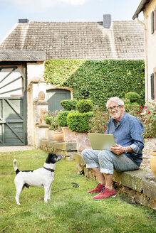 Portrait of smiling senior man with dog in garden using tablet - PESF01294