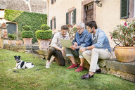 Three men of different age sitting in garden using tablet - PESF01297