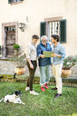 Three happy men of different age using tablet in garden - PESF01300