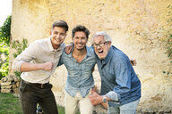 Portrait of three excited men of different age embracing and cheering in garden - PESF01306