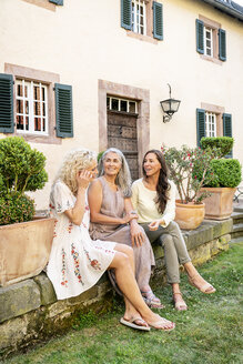 Three smiling women of different age sitting at country house talking - PESF01309