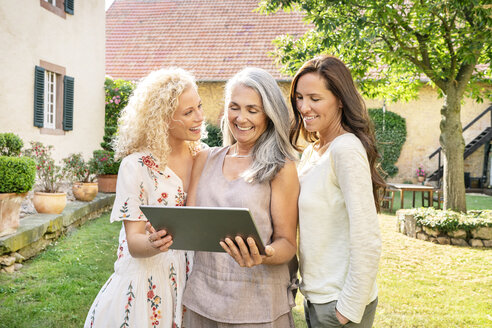 Three happy women of different age using tablet in garden - PESF01312