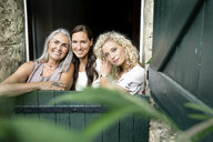 Portrait of three smiling women of different age behind stable gate - PESF01318