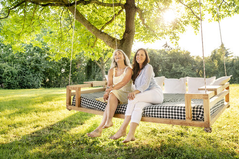 Two women relaxing on a hanging bed in garden - PESF01336