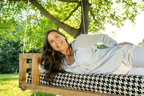 Mature woman relaxing on a hanging bed in garden - PESF01339