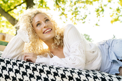Happy young woman lying on a bed in garden - PESF01345