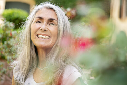 Portrait of happy woman with long grey hair in garden - PESF01351