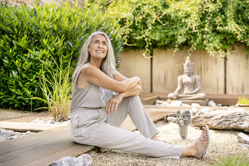 Smiling woman with long grey hair sitting on terrace in garden - PESF01360
