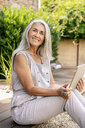 Smiling woman with long grey hair sitting on terrace in garden using tablet - PESF01363