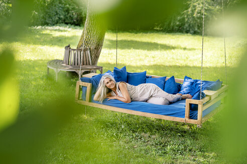 Smiling woman with long grey hair lying on a bed in garden - PESF01366