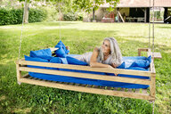 Smiling woman with long grey hair lying on a bed in garden - PESF01369