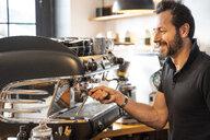 Smiling barista preparing coffee in a coffee shop - OCMF00268