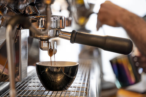 Close-up of barista preparing coffee in a coffee shop - OCMF00271