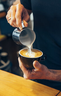 Close-up of barista preparing cappuccino in a coffee shop - OCMF00277
