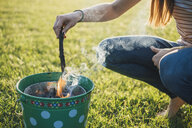 Woman barbecueing on a meadow, partial view - JSCF00124