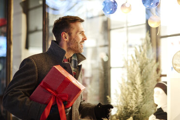 Smiling man with Christmas present looking in shop window - ABIF01157