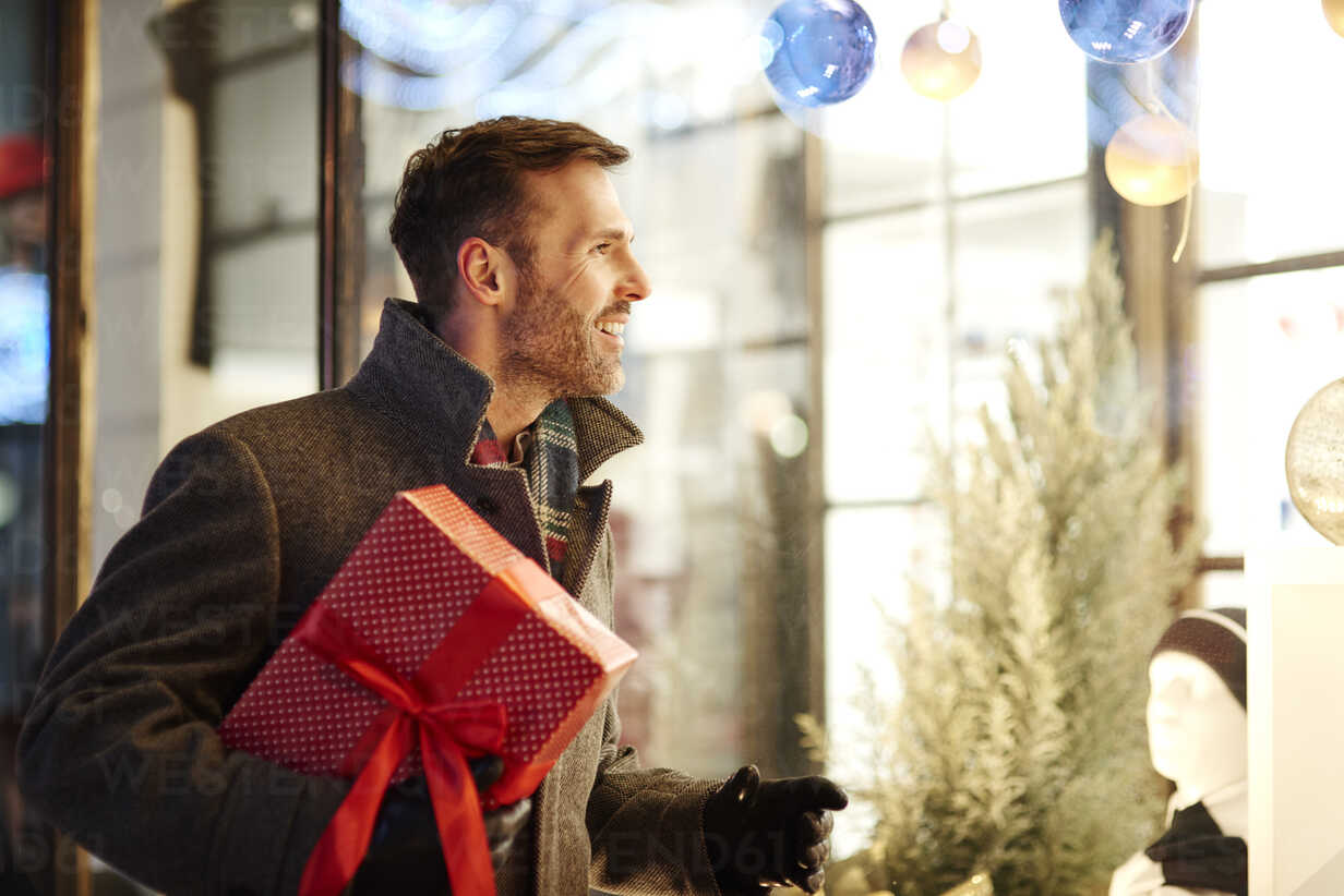 Smiling man with Christmas present looking in shop window - ABIF01157 - gpointstudio/Westend61