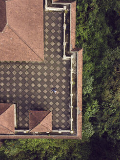 Indonesia, Bali, Aerial view of man on the roof terrace - KNTF02638