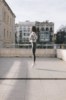 Young woman doing workout on terrace jumping in the air - JPF00344