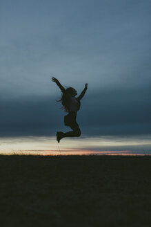 Silhouette of happy woman in nature jumping in the air at sunset - JPF00350