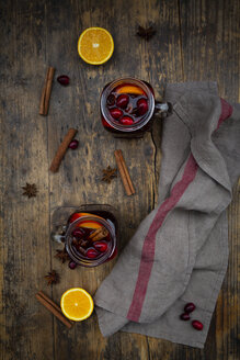 Glasses of mulled wine with cranberries, cinnamon sticks, orange and star anise on dark wood - LVF07757