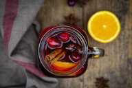Glass of mulled wine with cranberries, cinnamon sticks, orange and star anise on dark wood, focus on foreground - LVF07760