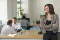 Smiling businesswoman in office with colleagues in background - PAF01863