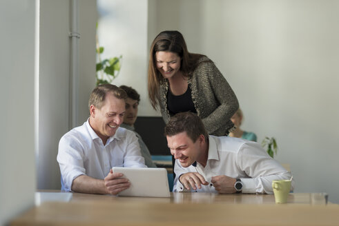 Happy colleagues looking at tablet in office - PAF01866