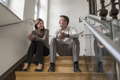 Smiling colleagues sitting in staircase talking - PAF01869