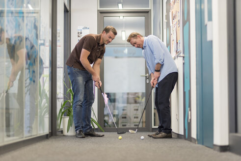 Two businessmen playing golf in office - PAF01902