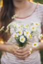 Woman holding bunch of picked white wildflowers, close-up - JSCF00142