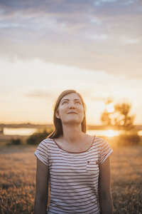 Portrait of young woman relaxing in nature at sunset - JSCF00151