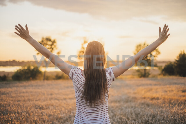 Back view of young woman watching sunset raising arms - JSCF00154