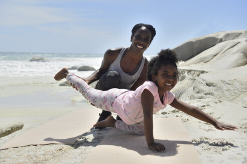 Mother and daughter doing a gymnastic exercise on the beach - ECPF00381