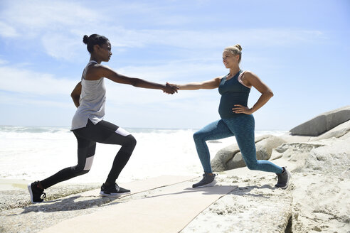 Two women doing a fitness exercise on the beach - ECPF00387