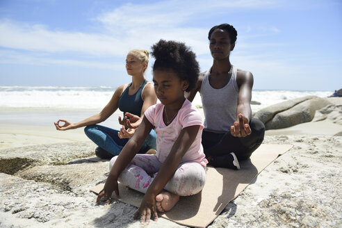 Mother with daughter and friend doing a yoga exercise on the beach - ECPF00393