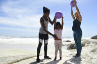 Mother with daughter and friend exercising with a ball on the beach - ECPF00399