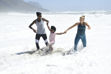 Mother with daughter and friend having fun in surf on the beach - ECPF00411