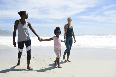Happy mother with daughter and friend walking on the beach - ECPF00414