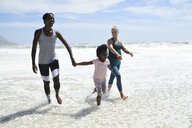 Mother with daughter and friend having fun in surf on the beach - ECPF00417