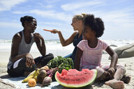 Mother with daughter and friend having a picnic on the beach - ECPF00423