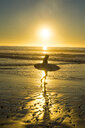 USA, California, Del Mar, Surfer at the beach at sunset - RUNF01132