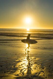 USA, California, Del Mar, Surfer at the beach at sunset - RUNF01132